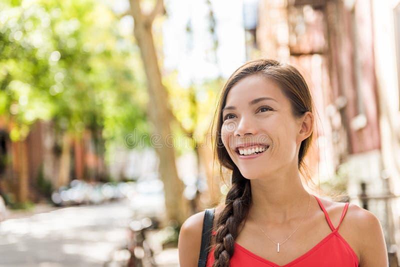Lycklig asiatisk kvinna som går i solig stadsgata royaltyfria foton