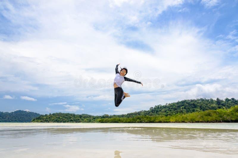 Lycklig asiatisk kvinna som hoppar gyckel på stranden arkivbilder