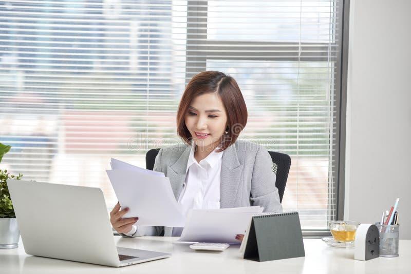 Lycklig asiatisk kvinna som i regeringsställning arbetar Kvinnligt gå till och med någon skrivbordsarbete på arbetsstället royaltyfria foton