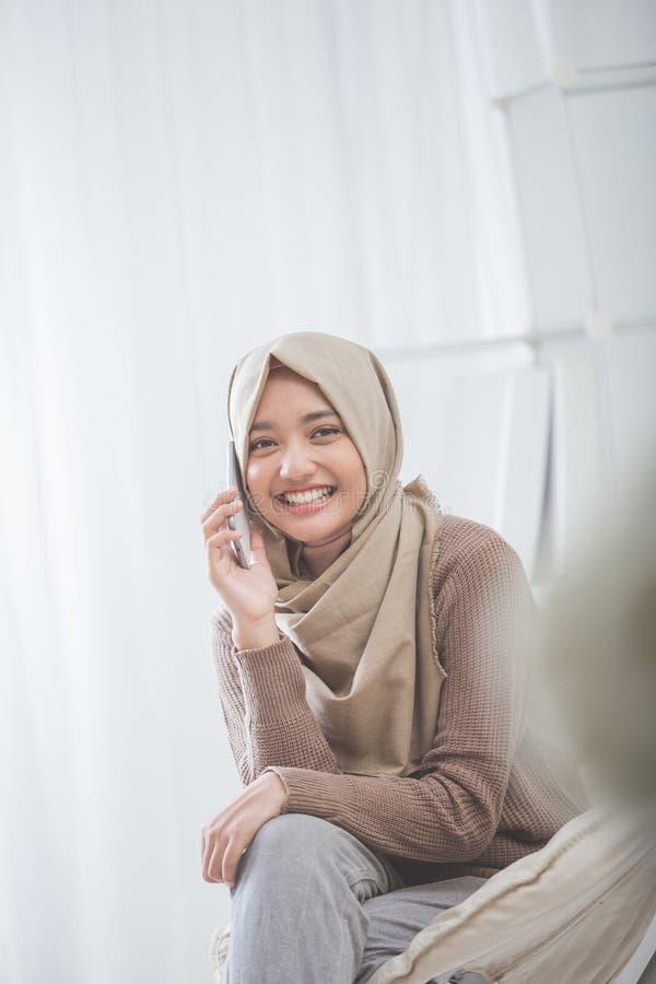 Lycklig asiatisk kvinna som kallar med mobiltelefonen fotografering för bildbyråer