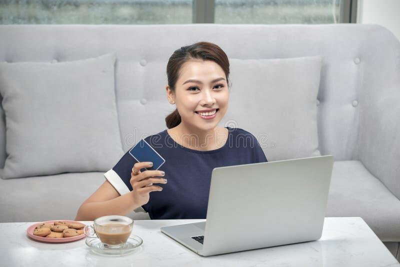 Lycklig asiatisk kvinna som ligger på golvmattan och direktanslutet hemma shoppar med kreditkorten och bärbara datorn Online-shop royaltyfri bild