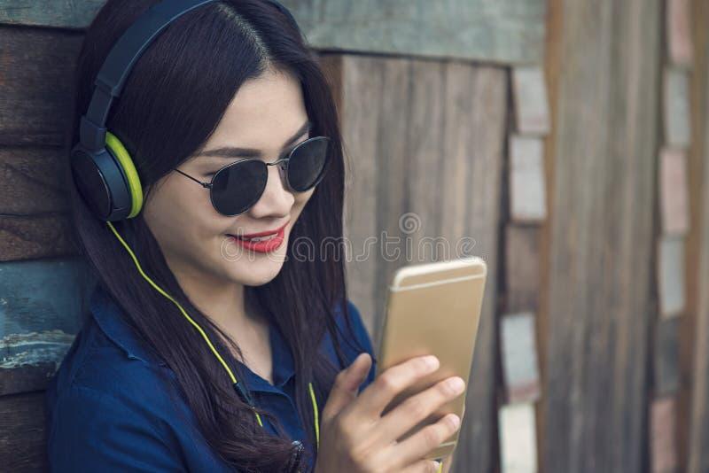 Lycklig asiatisk kvinna som lyssnar till musik på hennes headphone och watchi arkivbild
