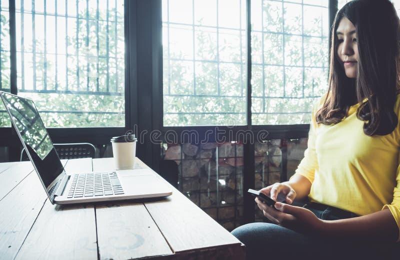 Lycklig asiatisk kvinna som pratar på hennes mobiltelefon, medan koppla av i kafé under fri tid, arkivbild