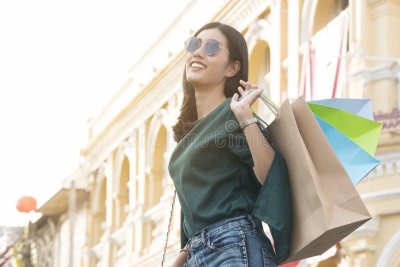 Lycklig asiatisk kvinna som rymmer shoppingpåsar i kineskvarter royaltyfri fotografi