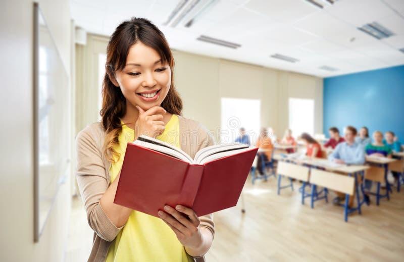Lycklig asiatisk kvinnaläsebok på skola royaltyfri foto