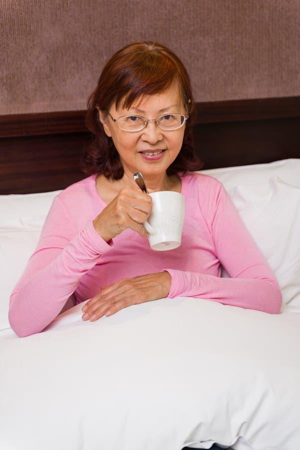 Lycklig asiatisk kvinnlig i säng royaltyfri foto