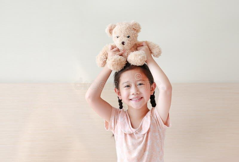 Lycklig asiatisk liten flicka som upp väljer bruna nallebjörnar på hennes huvud, medan sitta på sängen hemma fotografering för bildbyråer
