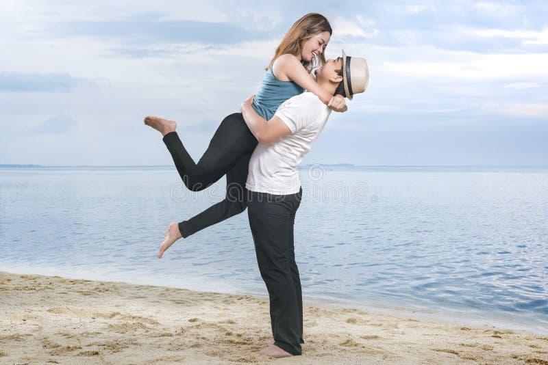 Lycklig asiatisk man i hatt som kramar hans flickvän på stranden royaltyfria foton