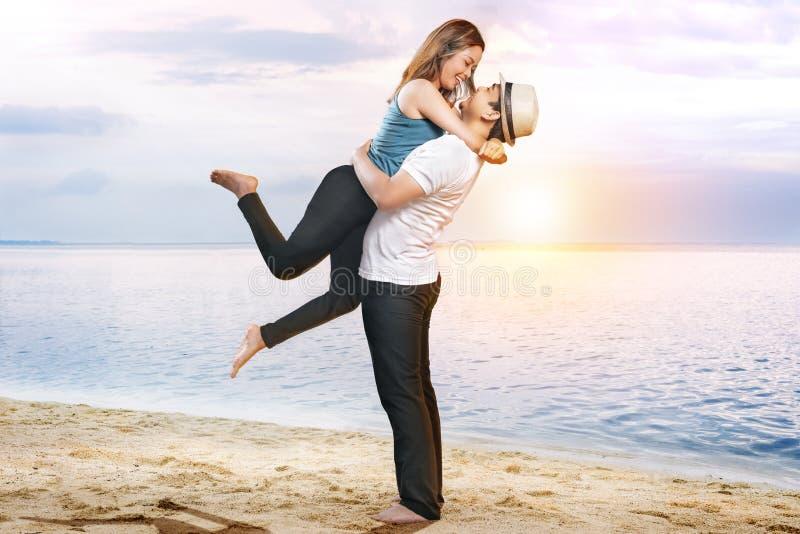 Lycklig asiatisk man i hatt som kramar hans flickv?n p? stranden fotografering för bildbyråer