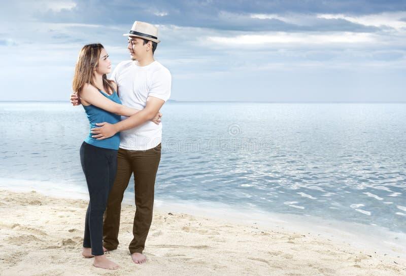 Lycklig asiatisk man i hatt som kramar hans flickv?n p? stranden royaltyfria bilder