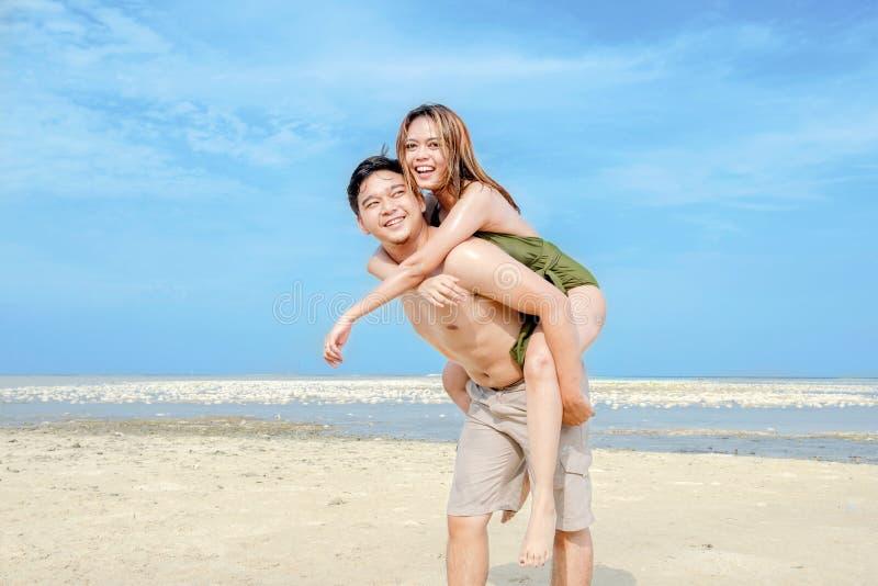 Lycklig asiatisk man som b?r en flicka p? hans baksida i stranden arkivfoton