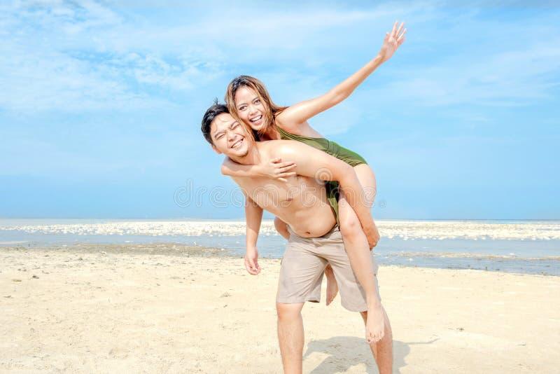 Lycklig asiatisk man som b?r en flicka p? hans baksida i stranden royaltyfri bild