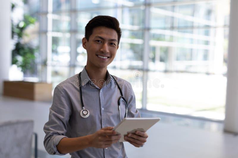 Lycklig asiatisk manlig doktor som använder den digitala minnestavlan i sjukhus royaltyfria bilder