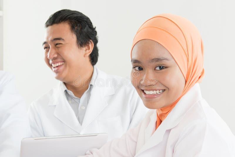 Lycklig asiatisk muslimsjuksköterska arkivfoto