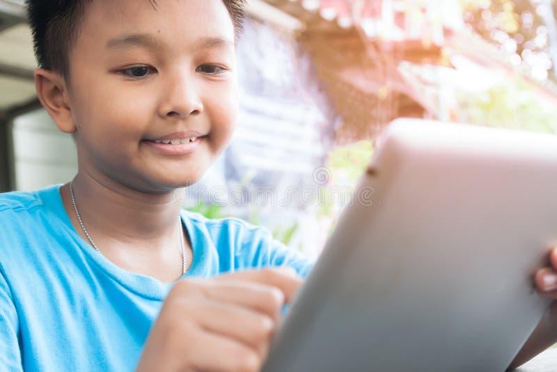 Lycklig asiatisk pojke som använder minnestavlan, och le som är utomhus- med solljus, barnet med teknologi och att knyta kontakt fotografering för bildbyråer