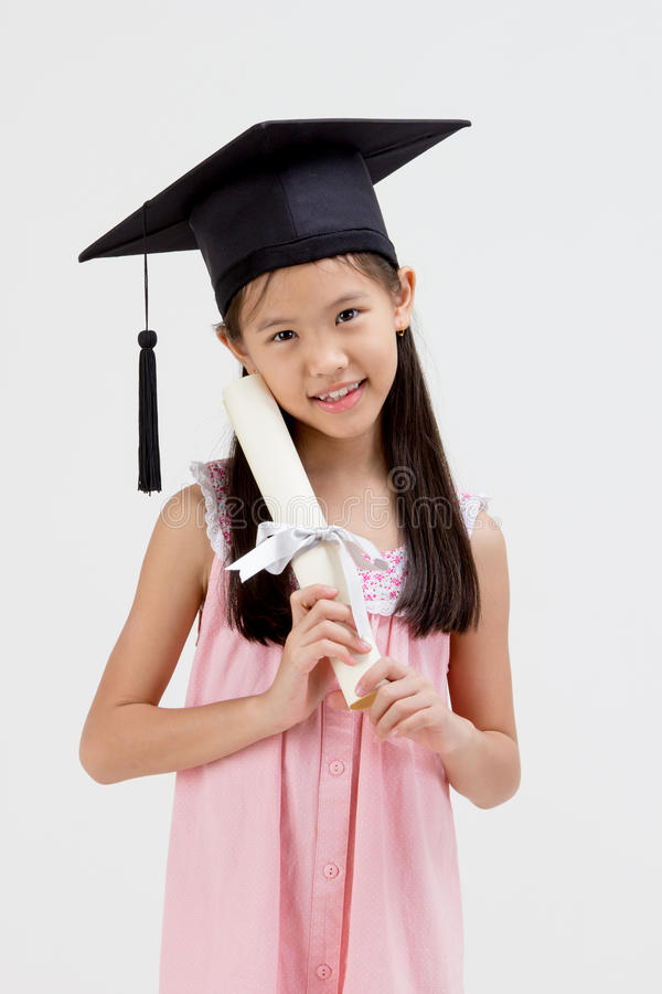 Lycklig asiatisk skolaungekandidat i avläggande av examenlock arkivbild