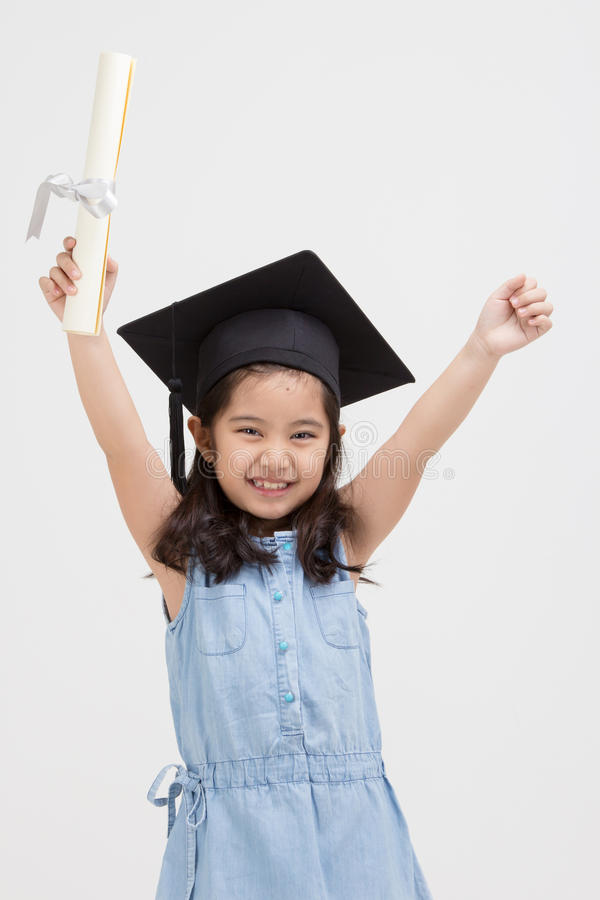 Lycklig asiatisk skolaungekandidat i avläggande av examenlock royaltyfri fotografi