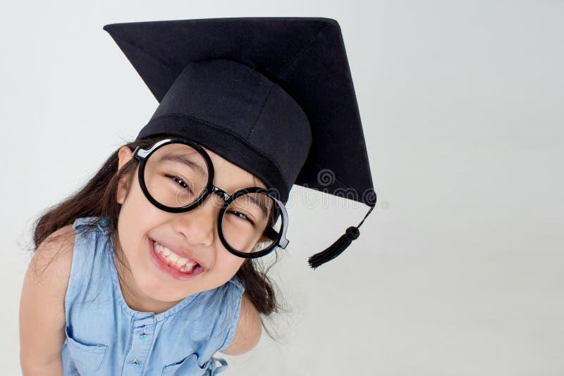 Lycklig asiatisk skolaungekandidat i avläggande av examenlock arkivfoton