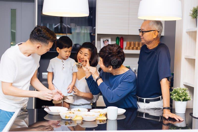 Lycklig asiatisk storfamilj som förbereder mat och hemma matar ett barn mycket av skrattet och lycka arkivfoto