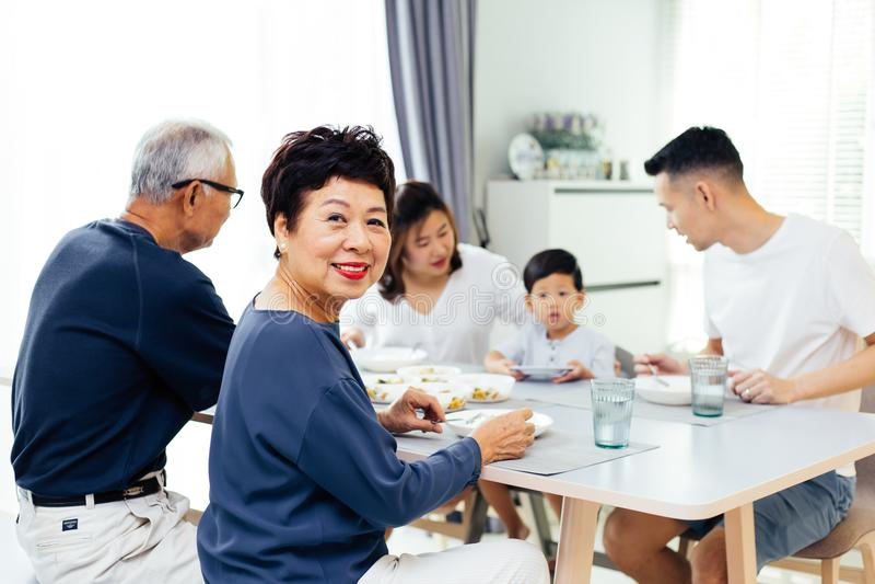 Lycklig asiatisk storfamilj som har matställen hemma mycket av lycka och leenden royaltyfri fotografi