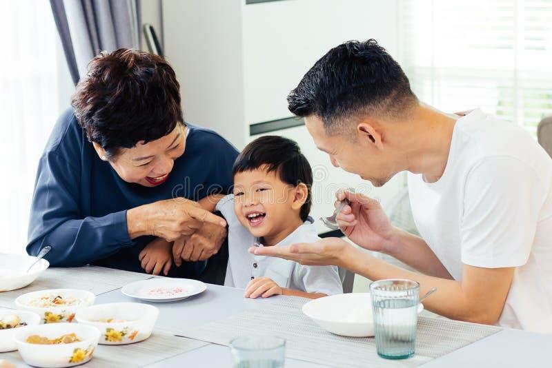 Lycklig asiatisk storfamilj som har matställen hemma mycket av skrattet och lycka royaltyfri fotografi