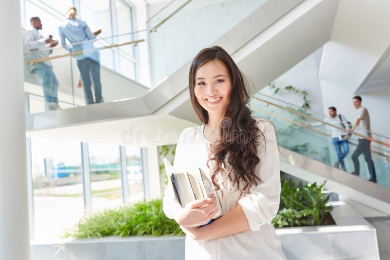 Lycklig asiatisk student med böcker royaltyfri fotografi