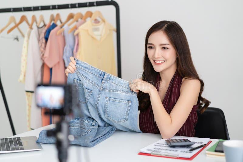 Lycklig asiatisk tillfällig härlig kvinnavlogger eller blogger som hemma sänder för trendmode för levande video online-nytt ämne  arkivbild