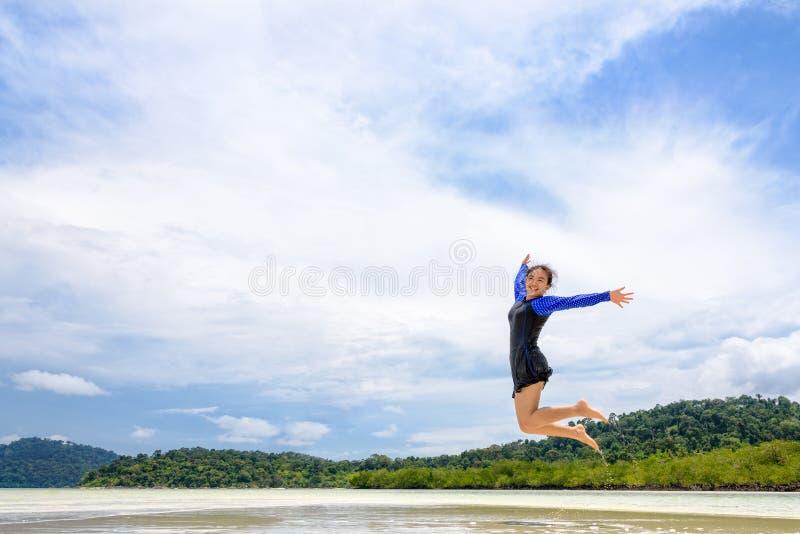 Lycklig asiatisk tonårig flicka som hoppar gyckel på stranden arkivfoton