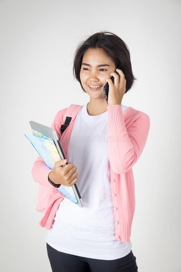 Lycklig asiatisk tonårs- student som kallar mobiltelefonen royaltyfria bilder