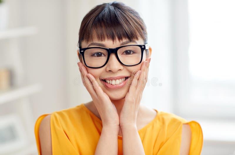 Lycklig asiatisk ung kvinna i exponeringsglas hemma arkivbild