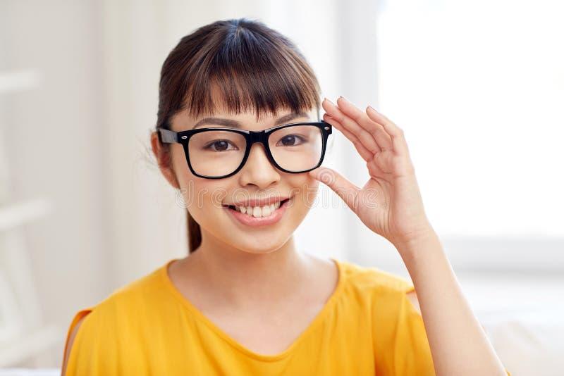 Lycklig asiatisk ung kvinna i exponeringsglas hemma royaltyfri foto