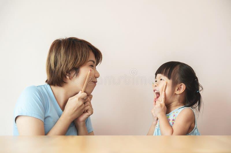 Lycklig asiatisk unge och hennes l?rare som har gyckel arkivbilder