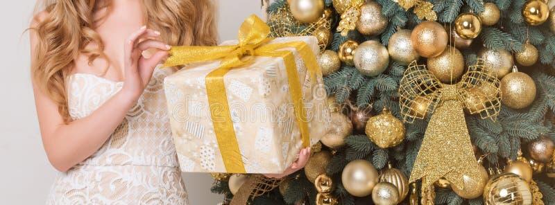 Lycklig ask för kvinnaöppningsgåva Lyxig blondin med julgåvan Berömtema för glad jul och för lyckligt nytt år Flickaholdin royaltyfri foto