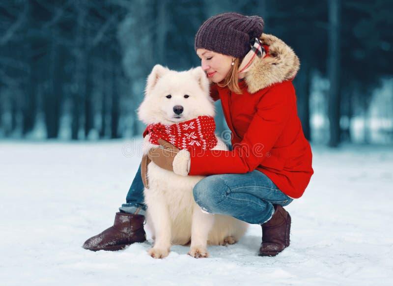 Lycklig att bry sig ung kvinna som omfamnar den vita Samoyedhunden i vinter royaltyfria foton
