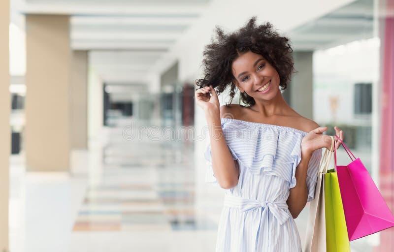 Lycklig attraktiv afrikansk amerikanshoppare i shoppinggalleria fotografering för bildbyråer
