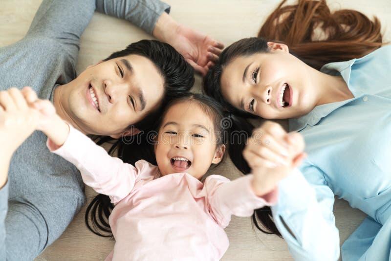 Lycklig attraktiv asiatisk familj med mamman, farsan och små gulliga unga elementära ungar för dotter som eller rymmer händer som fotografering för bildbyråer