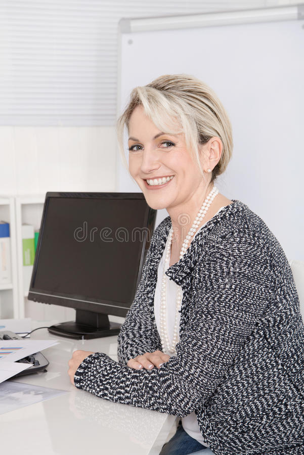 Lycklig attraktiv hög kvinnlig chef i ståendesammanträde på de royaltyfri foto