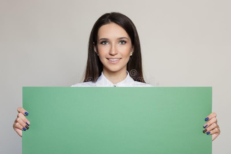 Lycklig attraktiv kvinna som rymmer det gröna mellanrumet royaltyfri bild