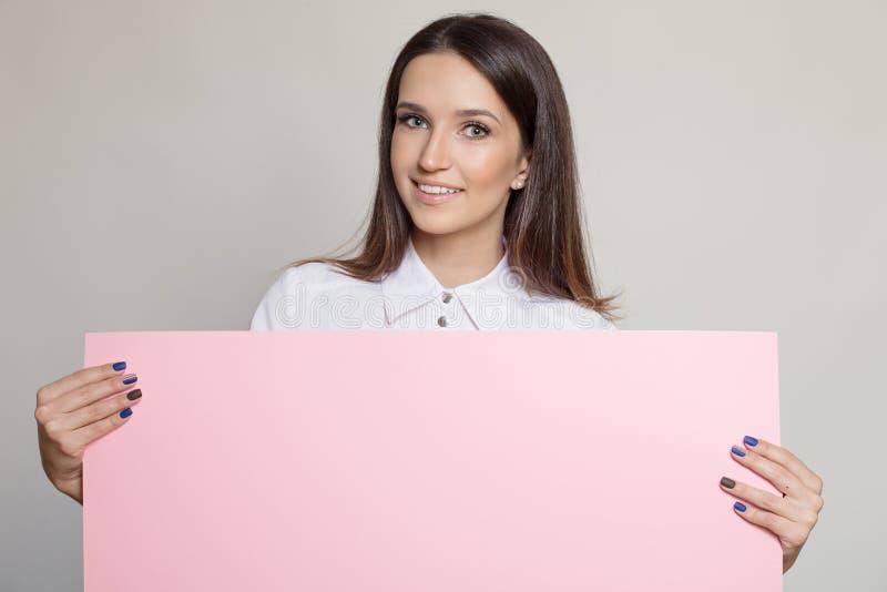 Lycklig attraktiv kvinna som rymmer det rosa mellanrumet royaltyfria bilder