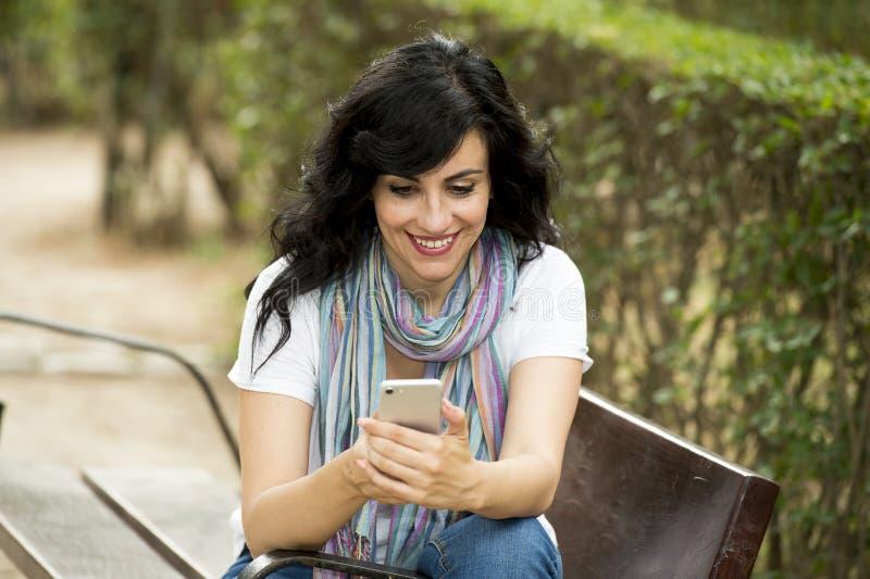 Lycklig attraktiv latinsk kvinna som talar och texing på hennes smarta telefon royaltyfria bilder