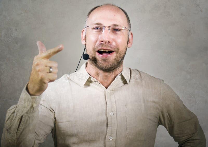 Lycklig attraktiv och säker affärsmanhögtalare med hörlurar med mikrofon som ger sig arbeta som privatlärare åt konferensutbildni royaltyfria bilder