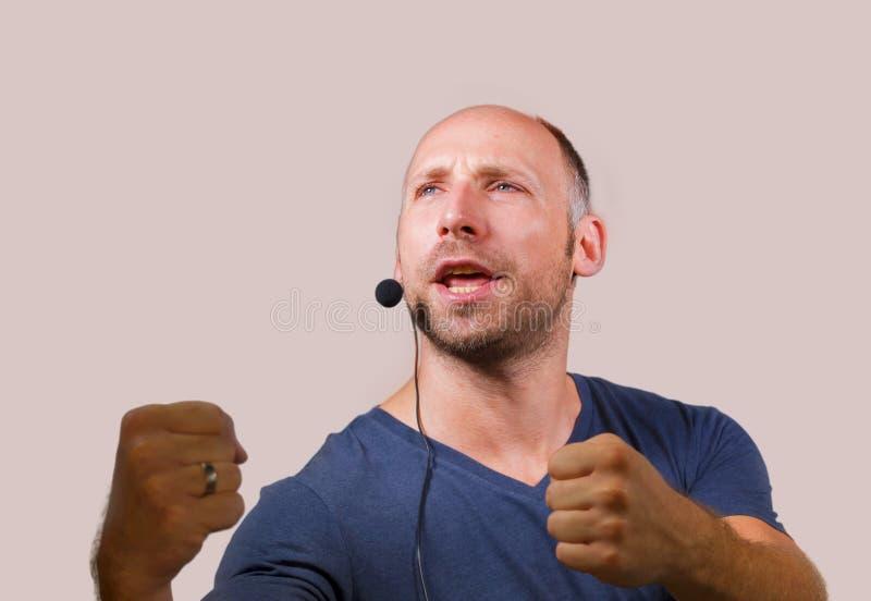 Lycklig attraktiv och säker affärsmanhögtalare med hörlurar med mikrofon som ger sig arbeta som privatlärare åt konferensutbildni royaltyfri fotografi