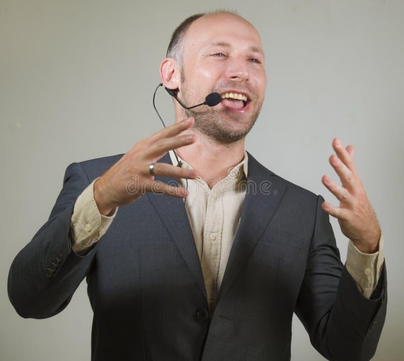 Lycklig attraktiv och säker högtalare för affärsman med hörlurar med mikrofon som ger sig arbeta som privatlärare åt konferensutb arkivfoton