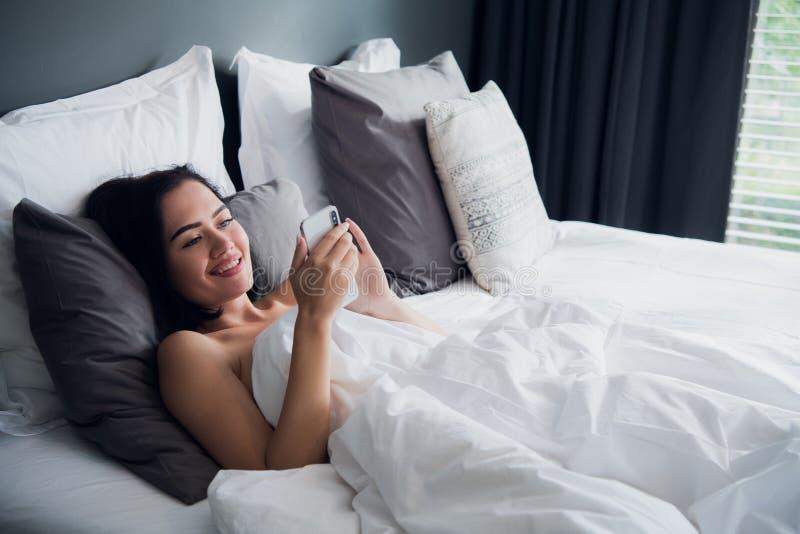 Lycklig attraktiv ung europeisk kvinnlig som i huvudsak ler, medan läsa textmeddelandet från hennes pojkvän som använder mobiltel arkivfoton