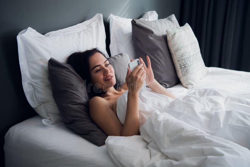 Lycklig attraktiv ung europeisk kvinnlig som i huvudsak ler, medan läsa textmeddelandet från hennes pojkvän som använder mobiltel royaltyfri bild