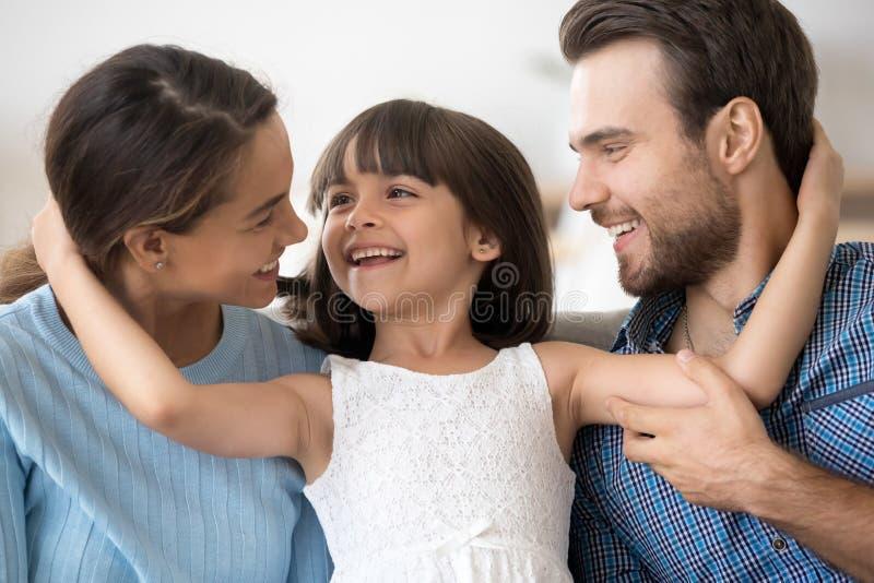 Lycklig attraktiv ung familj för stående som poserar att omfamna royaltyfria bilder