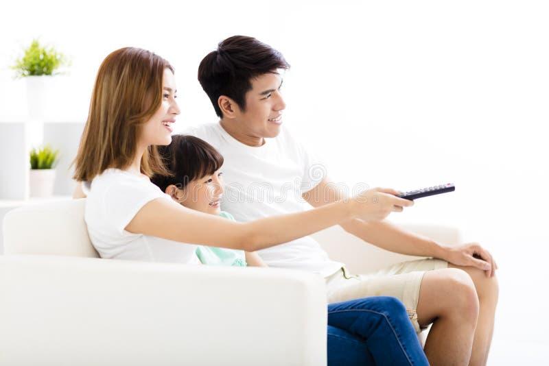 Lycklig attraktiv ung familj som håller ögonen på tv:n royaltyfri foto