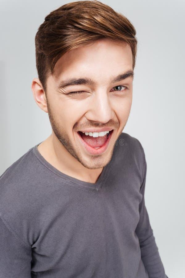 Lycklig attraktiv ung man i grått blinka för sweater arkivfoto