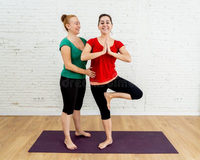 Lycklig attraktiv yogalärare som hemma undervisar yoga för ung kvinna i sund livsstil för kvinnor arkivfoton
