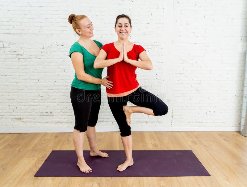 Lycklig attraktiv yogalärare som hemma undervisar yoga för ung kvinna i sund livsstil för kvinnor royaltyfria foton